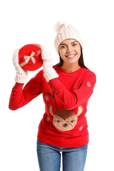 Молодая женщина в рождественском свитере и с подарком на белой поверхности
