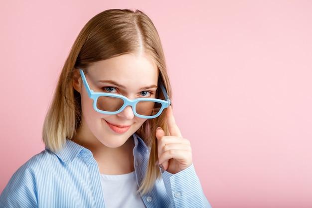 映画館で3d映画を見るためのシネマメガネの若い女性。コピースペースとピンク色の背景に分離されたメガネで笑顔のティーンエイジャーの女の子の肖像画の映画ビューア。
