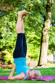 Молодая женщина в городском парке занимается йогой или разогревается для тренировки