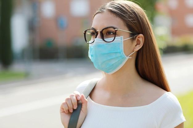 病気のウイルスsars-cov-2の拡散のための防護マスクを身に着けている都市通りの若い女性。
