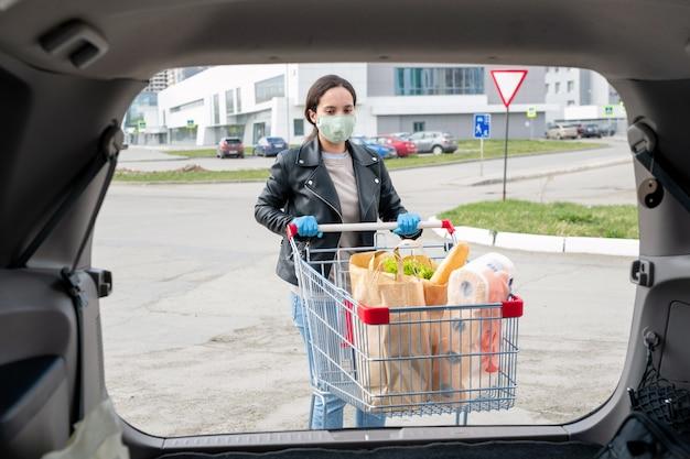 Молодая женщина в тканевой маске и перчатках подталкивает тележку к машине, чтобы загрузить продукты в багажник