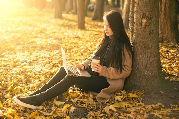 一杯のコーヒーとスマートフォンのラップトップでコートを着た若い女性