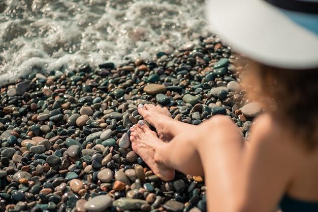 コピースペースで夏を楽しんでいる色のビキニと白い帽子の若い女性。海辺で日光浴の女性。夏休み、休日、リラックス。小石の海岸