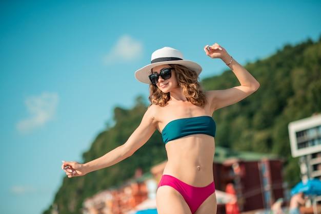Молодая женщина в бикини цвета, наслаждаясь летними танцами. женщина, загорающая на берегу моря. летние каникулы, каникулы, релакс. девушка загорает на пляже в купальнике