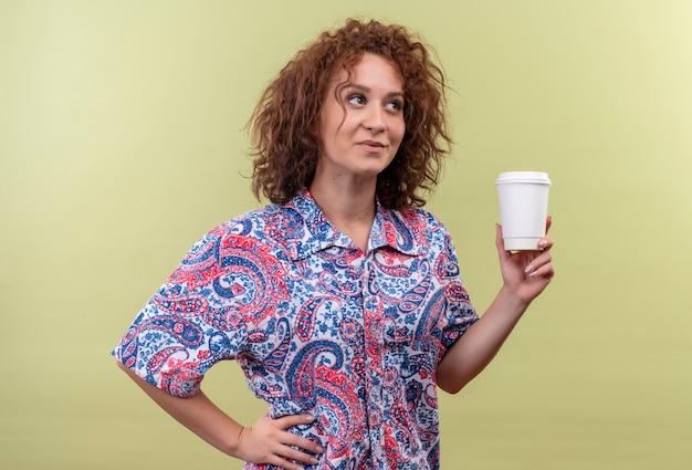 緑の壁の上に立って脇を見て微笑んでコーヒーカップを保持しているカラフルなシャツの若い女性