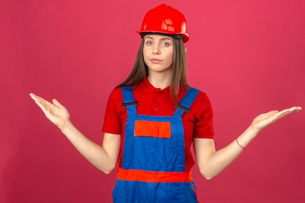 Молодая женщина в строительной форме и красный защитный шлем невежественным и растерянным выражением с поднятыми руками, не имея ни малейшего представления, стоя на темно-розовом фоне