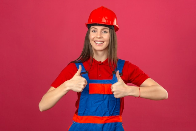 暗いピンクの背景の上に立って親指を示す幸せな探している制服と赤い安全ヘルメットの若い女性