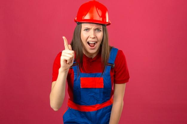 Молодая женщина в строительной форме и красный защитный шлем, указывая пальцем вверх с отличной идеей, вышел, глядя на камеру на темно-розовом фоне