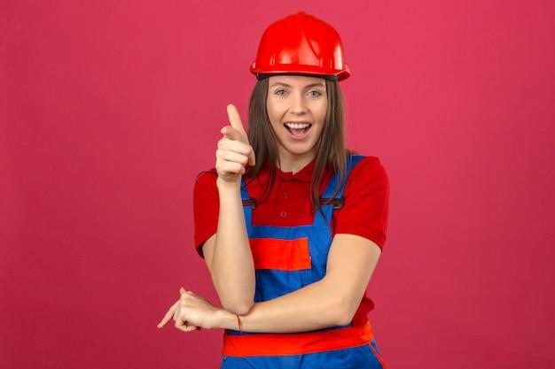 Молодая женщина в строительной форме и красный защитный шлем, улыбаясь и счастливый, глядя на камеру, стоя на темно-розовом фоне