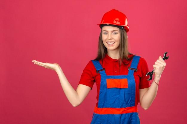 Молодая женщина в строительной форме и красный защитный шлем, улыбаясь, веселый, представляя и указывая ладонью и держа гаечный ключ на темно-розовом фоне