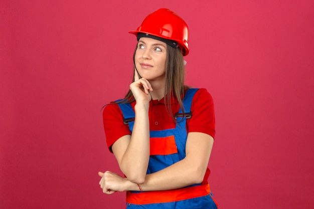 Молодая женщина в строительной форме и красный защитный шлем, улыбаясь, думая, новая идея, стоя на темно-розовом фоне