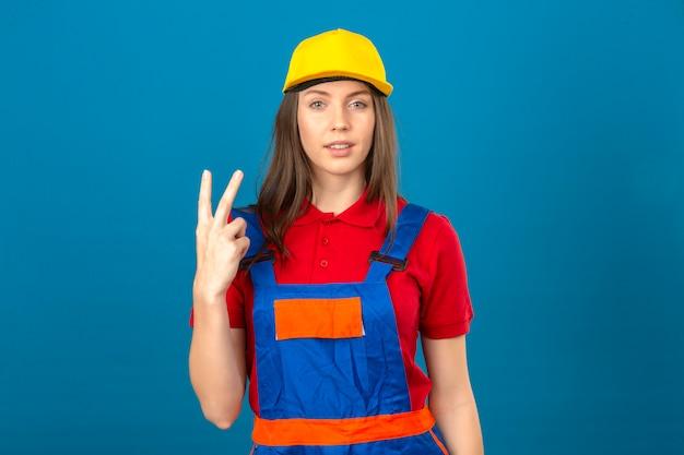 파란색 배경에 서 손가락으로 두 번째를 보여주는 카메라를 찾고 건설 균일하고 노란색 안전 헬멧에 젊은 여자