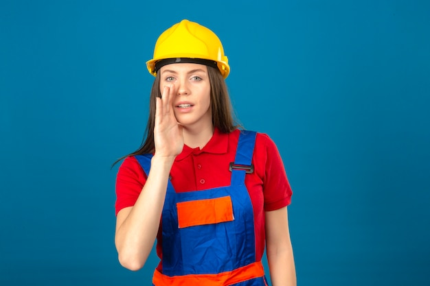 Молодая женщина в строительной форме и желтый защитный шлем с рукой возле рта, рассказывая секрет стоя на синем фоне