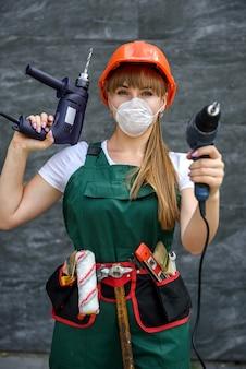 공구 벨트와 함께 포즈를 취하는 손에 드릴 기계와 작업복에 젊은 여자