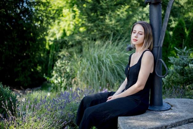 Молодая женщина в темном платье сидит возле цветов лаванды в саду