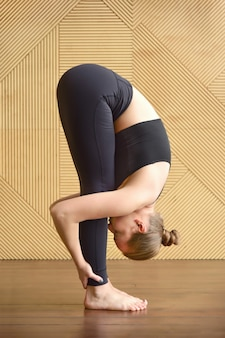 ウッタナサナのポーズで幾何学模様の木製の壁に立っている暗いスポーツウェアの若い女性