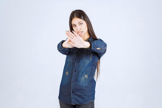 Молодая женщина в джинсовой ткани дает остановку чему-то