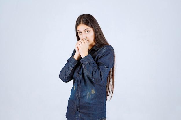 デニムシャツを着た若い女性は驚きと興奮を覚えます
