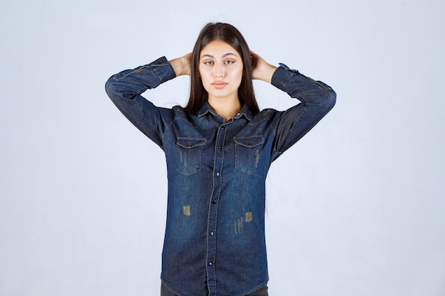 Молодая женщина в джинсовой рубашке принимает нейтральные и соблазнительные позы без реакции