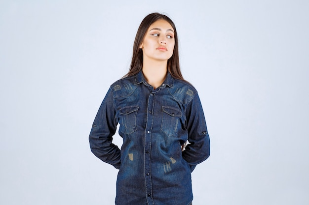 反応なしでニュートラルなポーズを与えるデニムシャツの若い女性