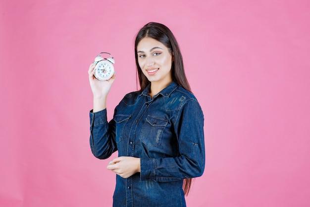 Молодая женщина в джинсовой рубашке держит и продвигает будильник