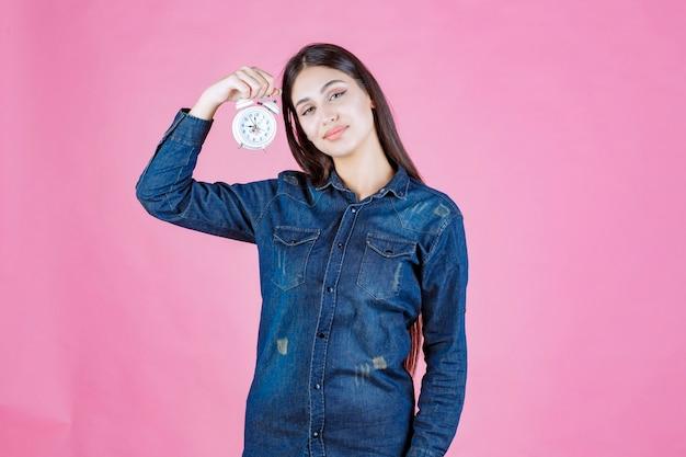 目覚まし時計を保持し、宣伝するデニムシャツの若い女性