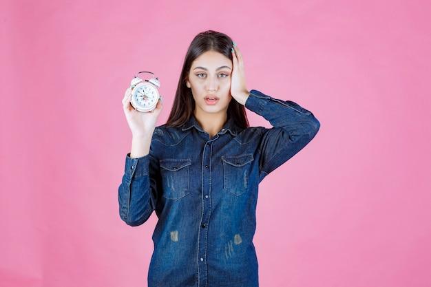 目覚まし時計を保持し、リングのために彼女の耳を覆っているデニムシャツの若い女性