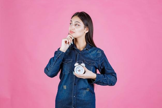 Молодая женщина в джинсовой рубашке держит будильник и думает
