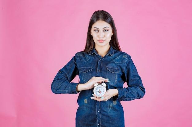 그녀의 손 사이에 알람 시계를 들고 데님 셔츠에 젊은 여자