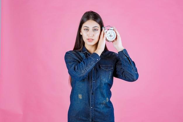 Молодая женщина в джинсовой рубашке держит будильник у уха и слушает