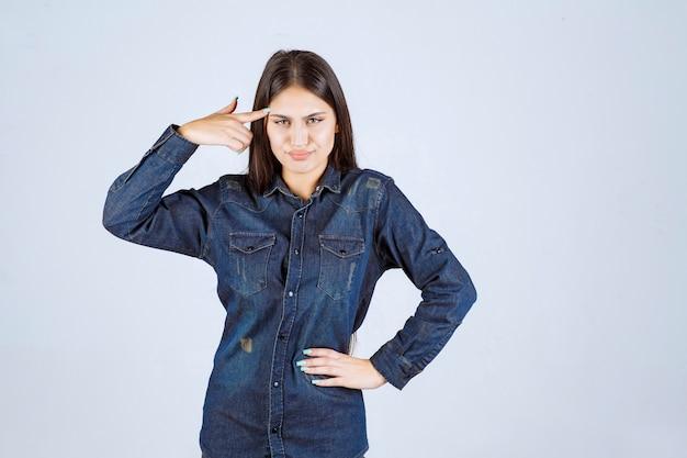 デニムシャツの若い女性は混乱して思慮深く見えます 無料写真