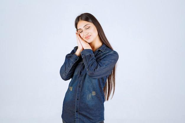 デニムシャツを着た若い女性は疲れ果てて眠そうに見えます