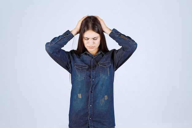 デニムシャツを着た若い女性は怖くて怖いように見えます