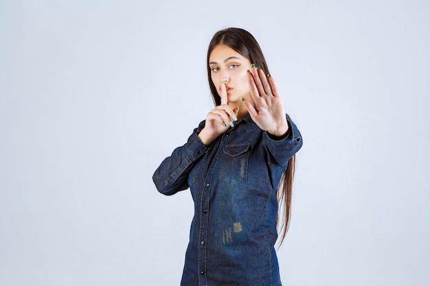 彼女の口を指して、静かにするように頼むデニムシャツの若い女性