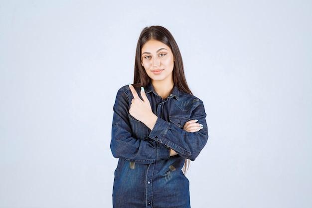뒤에 뭔가 가리키는 데님 셔츠에 젊은 여자