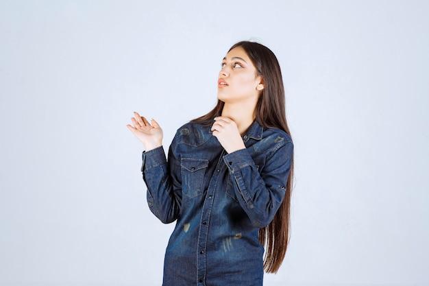 Молодая женщина в джинсовой рубашке, указывая на что-то позади