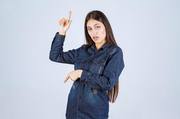 거꾸로 뭔가 가리키는 데님 셔츠에 젊은 여자