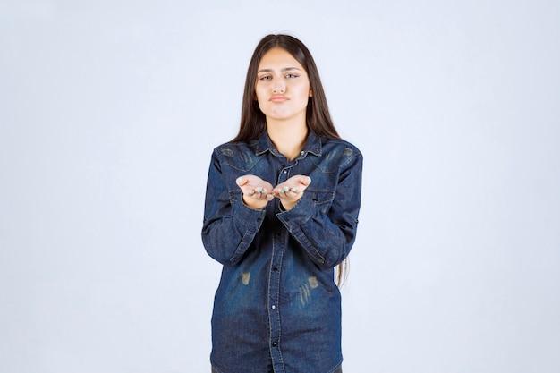 그녀 앞에서 사람을 가리키는 데님 셔츠에 젊은 여자