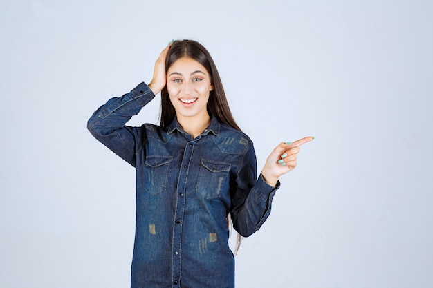 右側を指すデニムシャツの若い女性