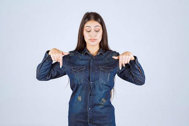 Молодая женщина в джинсовой рубашке, указывая на обратную сторону