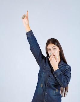 Молодая женщина в джинсовой рубашке поднимает руки вверх и указывает на что-то выше