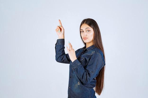 デニムシャツを着た若い女性が手を上げて、上の何かを指しています