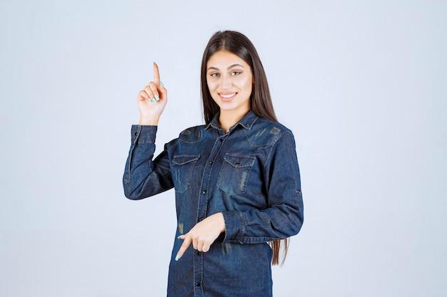 데님 셔츠에 젊은 여자가 그녀의 손을 위로 올리고 위의 것을 가리키는