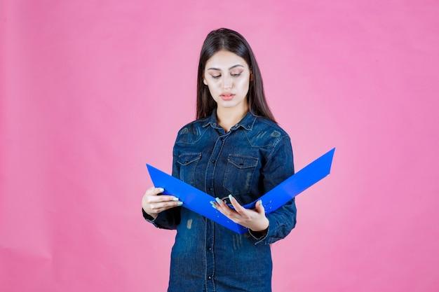 Молодая женщина в джинсовой рубашке читает отчеты