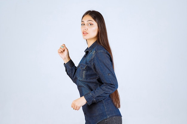 장소에서 실행하는 데님 셔츠에 젊은 여자