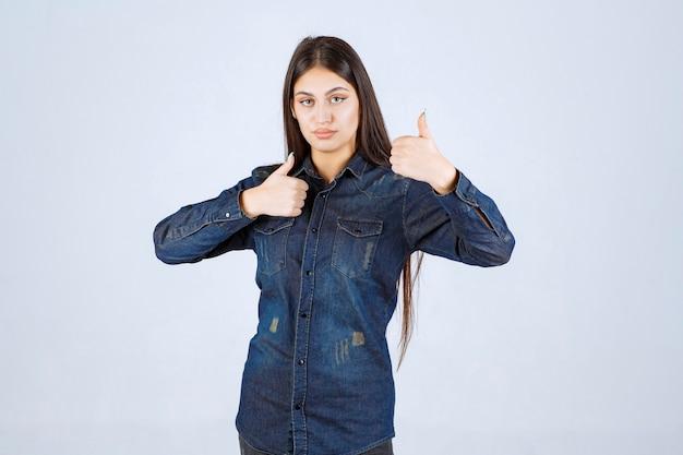 楽しさのサインを示すデニムシャツの若い女性