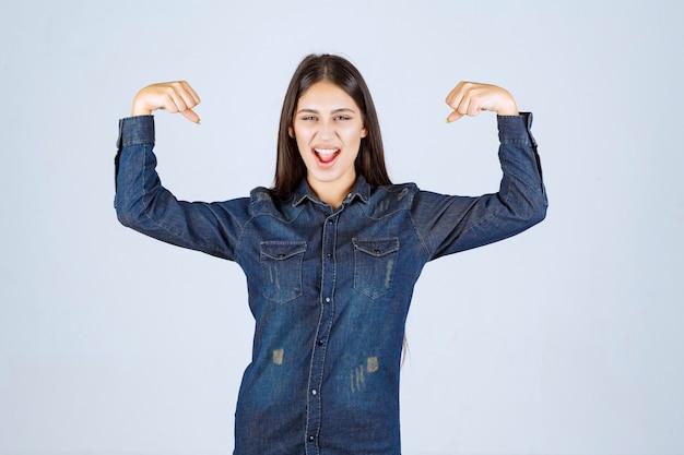 Молодая женщина в джинсовой рубашке показывает мышцы рук