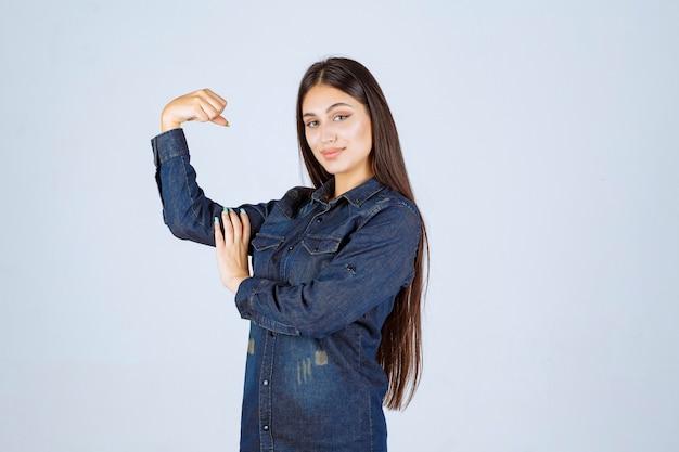 彼女の腕の筋肉を示すデニムシャツの若い女性