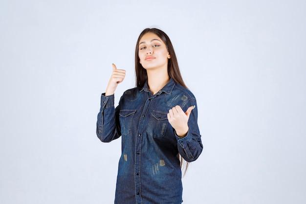 Молодая женщина в джинсовой рубашке показывает положительный знак рукой