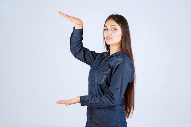 제품의 측정을 보여주는 데님 셔츠에 젊은 여자